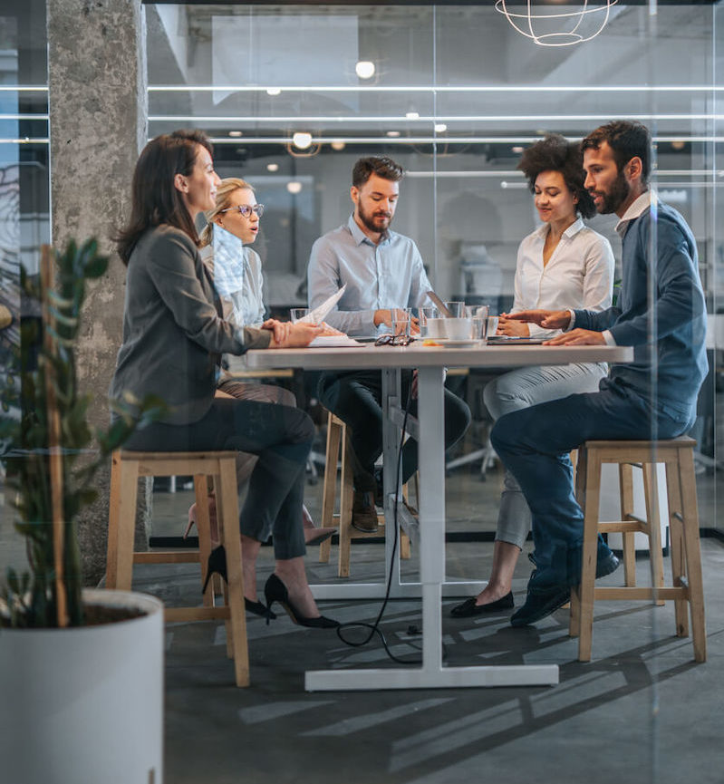 Side view of a table gathered with business people having a discussion